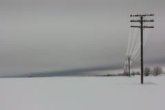 La corrente elettrica allinea con la brina sul palo elettrico di legno sulla campagna nell'inverno, Fotografie Stock Libere da Diritti