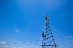 La corrente elettrica cabla gli elettricisti delle riparazioni della torre fotografie stock libere da diritti