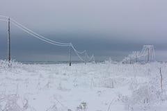 La corrente elettrica di fase rotta allinea con la brina sui pali elettrici di legno sulla campagna nell'inverno dopo la tempesta Immagini Stock