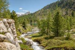 La corrente sfocia nel lago della montagna immagini stock