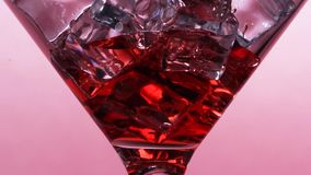 La corrente sottile di vino rosso o di Juice Or An Alcoholic Cocktail è versata in un vetro archivi video