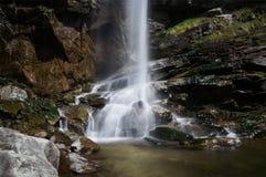 La corriente blanca del agua salpica en la roca de fondo debajo de un acantilado Fotos de archivo libres de regalías