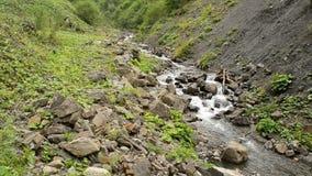 La corriente del agua en montañas fluye entre las colinas rocosas en verano metrajes