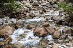 La corriente hermosa de la montaña atraviesa el cauce del río pedregoso, rocoso fotografía de archivo