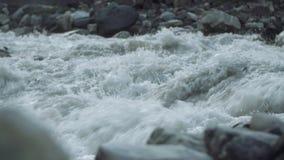 La corriente pedregosa de los rápidos del río salvaje de la montaña con blanco salpica almacen de video