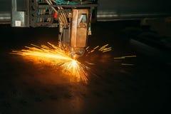 La cortadora del laser con las chispas se cierra para arriba foto de archivo