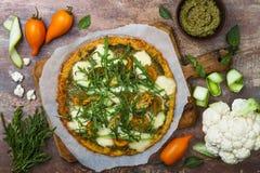 La corteza de la pizza de la coliflor con pesto, los tomates amarillos, el calabacín, el queso de la mozzarella y la calabaza flo Fotografía de archivo