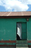 La cortina blanca sopla de puerta de la casa verde imagen de archivo