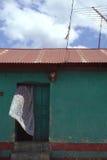 La cortina blanca sopla de puerta de la casa verde con la antena Imagen de archivo