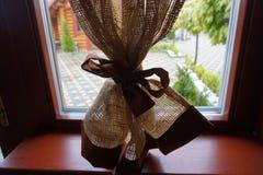 La cortina en la ventana se ata con una cinta marrón fotos de archivo libres de regalías