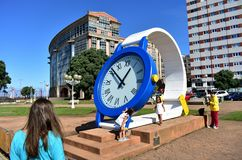Woman looking at the time in a giant clock with children. Public park close to Riazor Beach. La Coruna, Spain, 22 Sep 2018. La Coruna, Galicia, Rias Altas stock photo