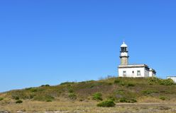 Old abandoned lighthouse on a hill. Sunny day, Galicia, Spain. royalty free stock image