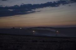 La cosecha de la noche, máquinas segadores está cosechando en un campo de trigo Fotos de archivo libres de regalías