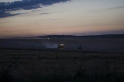 La cosecha de la noche, máquinas segadores está cosechando en un campo de trigo Imagen de archivo libre de regalías