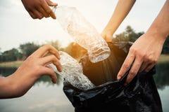 La cosecha voluntaria para arriba un plástico de la botella en el río fotografía de archivo
