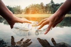 La cosecha voluntaria para arriba un plástico de la botella en el río fotografía de archivo libre de regalías