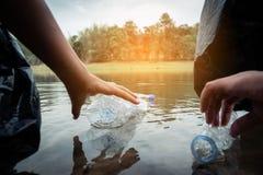 La cosecha voluntaria para arriba un plástico de la botella en el río fotos de archivo libres de regalías