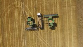La cosechadora descarga el grano en el camión almacen de metraje de vídeo