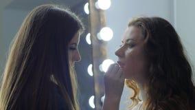 La cosmetología, estilista hace maquillaje de moda a la hembra en salón de belleza almacen de video