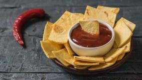 La cosse du piment avec des puces de tortilla mexicaines et un bol de sauce Images stock