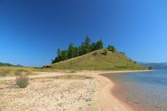 La costa del lago Baikal, la roccia con gli alberi Fotografie Stock