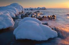 La costa del mar frío del invierno en la puesta del sol Imagen de archivo libre de regalías