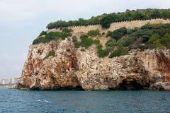 La costa del mare Belle scogliere sopra il blu la parete della fortezza di Alanya, vista dal mare Immagini Stock Libere da Diritti