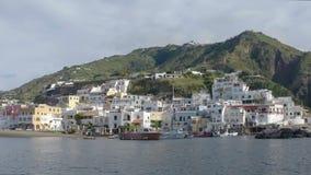 La costa dell'isola con le case bianche ha costruito densamente sulla collina, vista dall'altro lato del porto archivi video