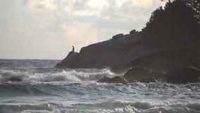 La costa que se estrella de la onda ventosa del mar oscila durante puesta del sol con el pescador en fondo almacen de video