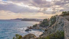 La costa rocciosa del mare, della città e del cielo Fotografia Stock Libera da Diritti