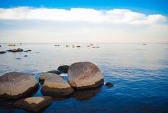 La costa rocciosa e le acque calme del mare Fotografia Stock Libera da Diritti