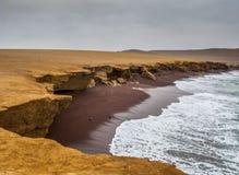La costa y la playa roja de la arena de la reserva nacional de Paracas Imagen de archivo libre de regalías