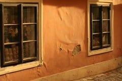 La costruzione abbandonata con l'arancia ha rotto la facciata e le belle finestre di legno marroni Fotografia Stock
