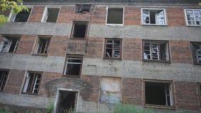 La costruzione abbandonata ha finestre rotte anellate con i cocci delle strisce di vetro e stracciate di tela da imballaggio che  archivi video