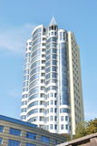 La costruzione bianca alta è contro il cielo blu-chiaro Fotografie Stock Libere da Diritti