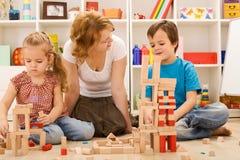 La costruzione con i blocchi di legno è insieme divertimento Immagini Stock