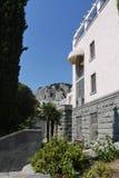 La costruzione del complesso del sanatorio con un bello balcone e delle palme sotto contro lo sfondo di un livello Fotografia Stock