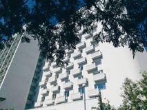 La costruzione dell'hotel, nascosta dai rami di un albero, Kiev, Ucraina Fotografia Stock