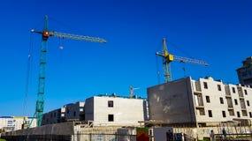 La costruzione delle case Alta gru al cantiere Fotografia Stock