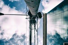 La costruzione di affari con le nuvole ha riflesso sulle finestre e sul palo elettrico Fotografie Stock Libere da Diritti