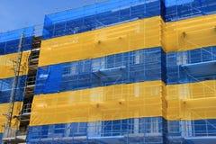 La costruzione di appartamento con una rete blu e gialla è in costruzione di estate Fotografie Stock