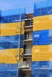 La costruzione di appartamento con una rete blu e gialla è in costruzione di estate Immagine Stock Libera da Diritti