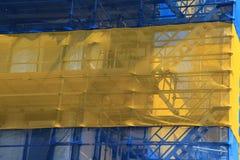 La costruzione di appartamento con una rete blu e gialla è in costruzione di estate Fotografia Stock Libera da Diritti