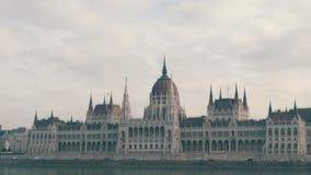 La costruzione di fama mondiale del Parlamento a Budapest ha costruito nel gotico nei precedenti di un aeroplano che vola da sopr stock footage