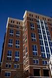 La costruzione di mattone alta con il blu ha tinto il coverd delle finestre da due lati con cielo blu croccante. fotografia stock libera da diritti