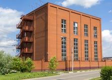La costruzione di piccola fabbrica del mattone rosso Costruzione di produzione con i balconi fotografie stock