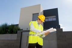 La costruzione di sorveglianza del giovane lavoratore attraente del caporeparto blueprints il casco all'aperto d'uso della costru Immagini Stock