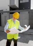 La costruzione di sorveglianza del giovane lavoratore attraente del caporeparto blueprints il casco all'aperto d'uso della costru Fotografia Stock Libera da Diritti