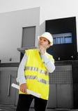 La costruzione di sorveglianza del giovane lavoratore attraente dell'architetto blueprints il casco all'aperto d'uso della costru Fotografie Stock Libere da Diritti