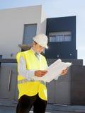 La costruzione di sorveglianza del giovane lavoratore attraente dell'architetto blueprints il casco all'aperto d'uso della costru Immagine Stock